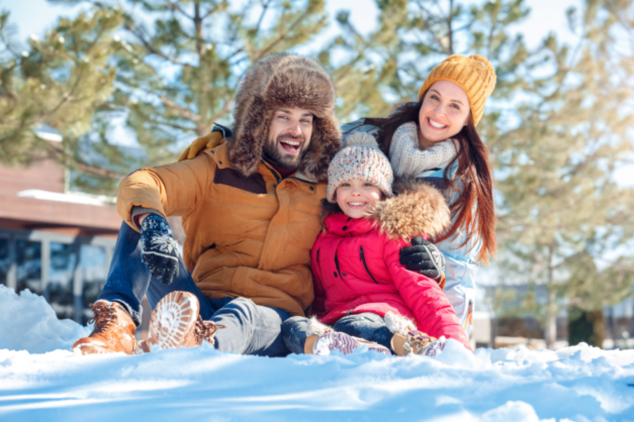 Family smiling while playing in snow