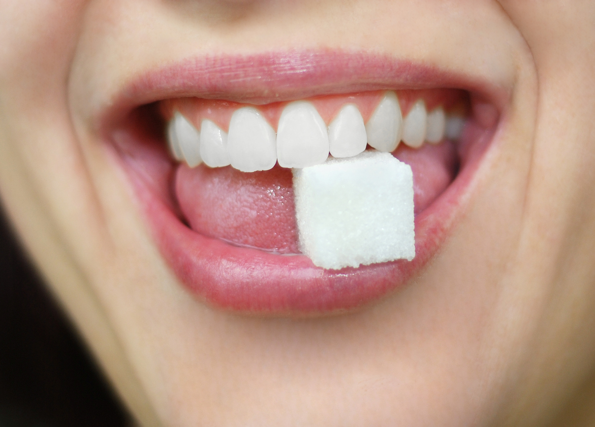 Close up of a woman holding a sugar cube between her teeth in her mouth.